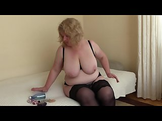A mature milf with big tits pushes a bottle out of a hairy pussy