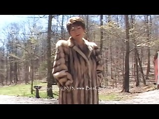 Beautiful mature lady takes off a luxurious fur coat outdoors