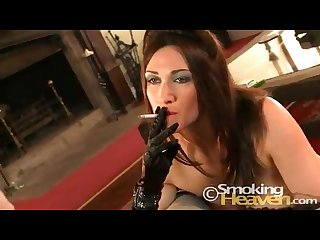 Elegant brunette smoking a cigarette while giving a blowjob