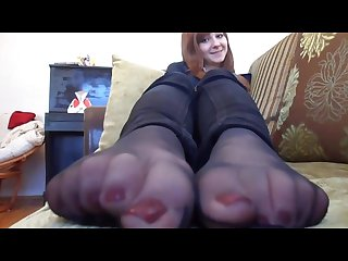 Cute girl relaxes her nylon feet on the sofa
