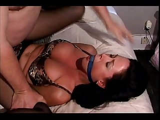 Dark haired woman in pantyhose is gagged tied up and forced to fuck
