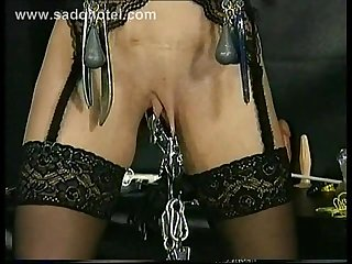 Master puts large metal clamps with weights on pussy lips and nipples of slave and spanks her